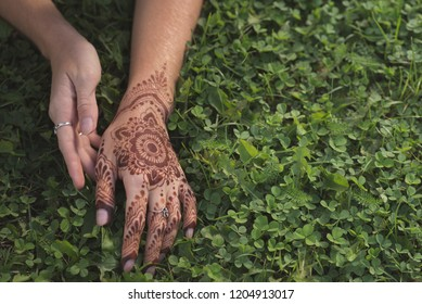 Female hands with mehendi drawings among floral background. Bright summer pictures.