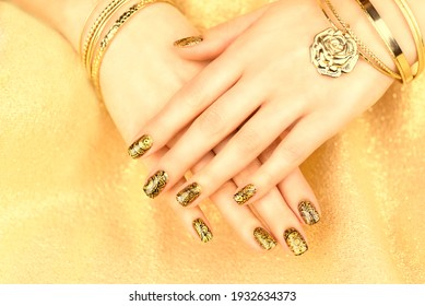 Female hands with mehendi style manicure. Beautiful golden manicure on a golden background.