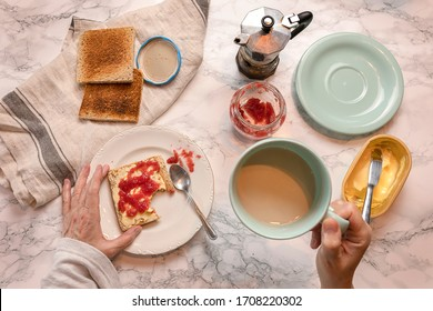 Female hands with milk and coffee cup and toast with butter and marmalade. From above.