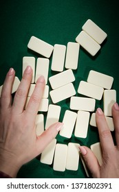 Female hands mixing domino bones on a table covered with green cloth