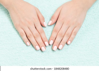 Female hands with new manicure. Hands with pink nail polish on a pastel green towel. Care for woman hands. Woman in salon receiving manicure by nail beautician.