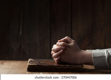 Female hands on Bible over wooden background