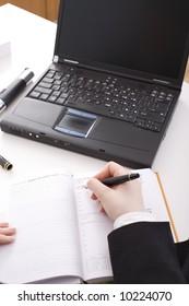 Female hands on the desk / laptop, calendar