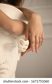 female hands on the head of an antique bust