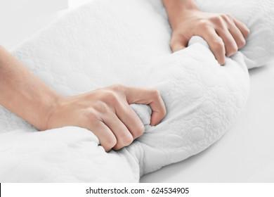 Female hands on orthopedic pillow, closeup