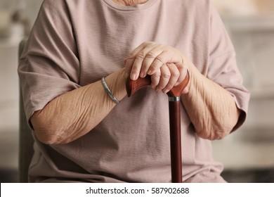 Female hands on walking stick closeup