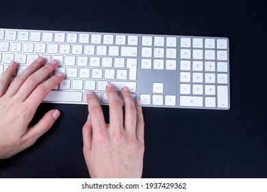 Female hands on the white keyboard on black baground. Typing, writing, freelance and working from home keyboard.