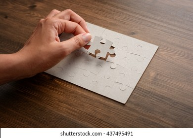 Female hands on a wooden office desk pick puzzle. Macro with blur, soft focus, vignette