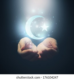 Female hands opening to light and half moon and star, symbol of islam religion