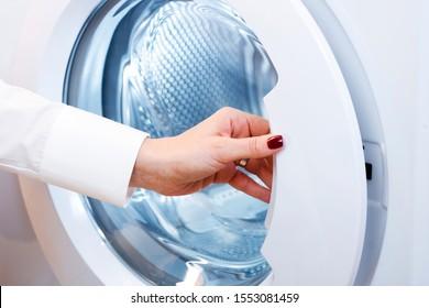 Female hands opening washing machine