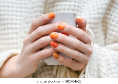 Female hands with orange nail design holding white cup.