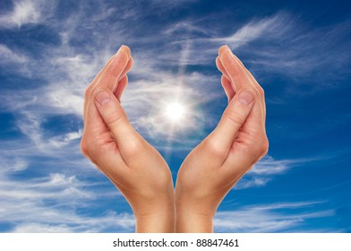 female hands over blue sky with clouds - religion and environment protection concept