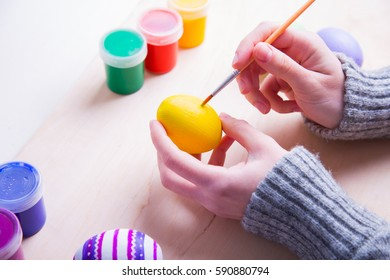 Female hands painting wooden easter egg with brush.