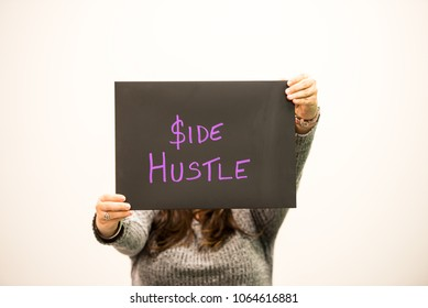 Female hands and part of body holding up a black rectangular chalkboard sign with the words side hustle in purple handwritten letters for entrepreneur concept
