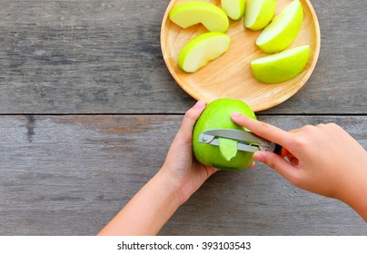 Female hands peeling skin off of green apple using a paring knife with bamboo plate wooden table in background