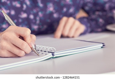 Female hands with pen writing on notebook at white office table.