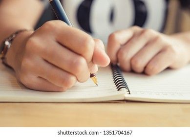 female hands with pen writing on notebook - Image