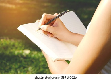 Female hands with pen writing on notebook in park