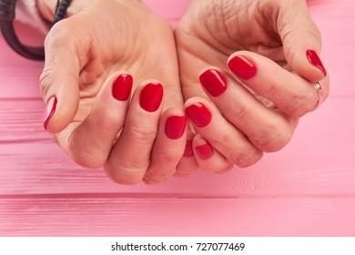 Female hands with perfect red nails. Hands of senior woman with beautiful red manicure on pink wooden background close up. Perfect manicure concept.