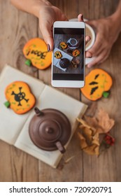 Female hands photographing a table with Halloween biscuits and coffee on their phone