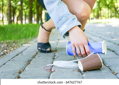 Female hands picking up trash outdoors in the street in summer