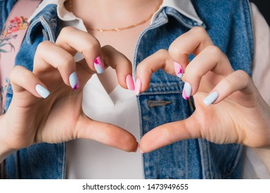 Female hands with a pink and blue manicure in the shape of a heart.