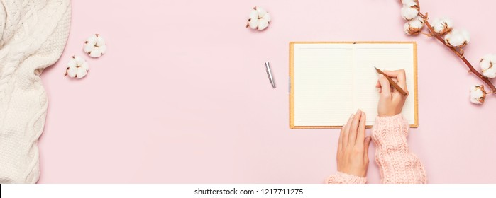 Female hands in pink knitted sweater written with a pen in open clean notebook and cotton on pink pastel table top view flat lay Fashion blogger working desk Cotton flowers Lifestyle gentle background