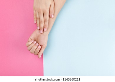 female hands with pink manicure on pink and blue pastel background