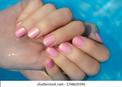 Female hands with pink nail design. Pink nail polish manicured hands. Female hands in blue pool water