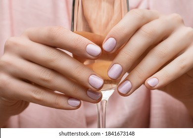Female hands with pink nail design. Pink glitter nail polish manicure. Woman hands hold champagne glass.