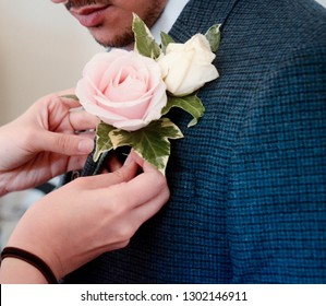 Female hands pinning a rose buttonhole onto the groom at a wedding