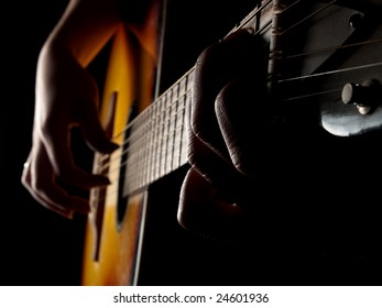 Female hands playing acoustic guitar on black background