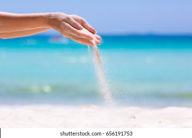 Female hands playing in white sand on the beach on blue sea background