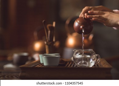 Female hands pouring tea from a teapot closeup