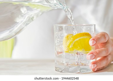 Female hands pouring water from the decanter into a glass beaker with lemon and ice. Health and diet concept. Quenching thirst on a hot day.