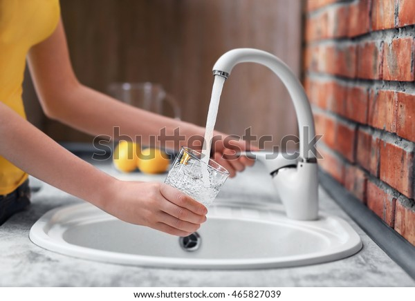 Female hands pouring water in glass cup