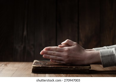 Female hands praying on Bible