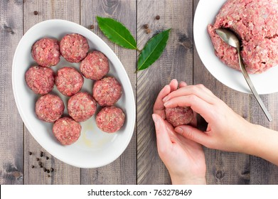 Female hands prepare meatballs on the wooden table, top view
