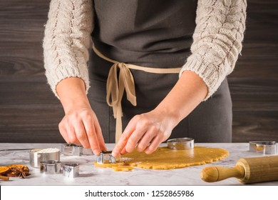 Female hands preparing Christmas cookies. Raw dough and cookie cutters on marble kitchen tabletop.