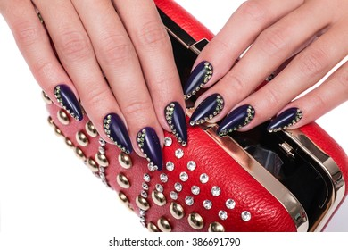 Female hands with purple manicure with rhinestones holding a red handbag