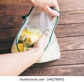 Female hands putting fresh corn cob in reusable eco mesh bag. Zero waste and no plastic concept.
