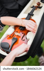 Female hands are putting wooden violin in open holster - Shutterstock ID 1846062124