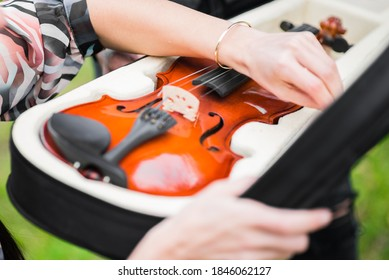 Female hands are putting wooden violin in open holster - Shutterstock ID 1846062127