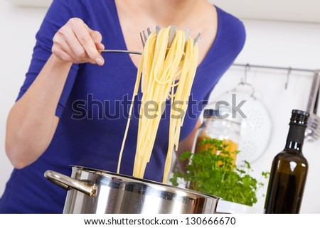female hands raising cooked spaghettis out of the pot