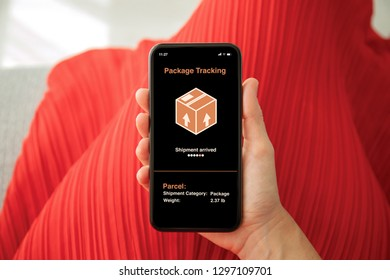 female hands in red dress holding phone with app tracking delivery package on the screen