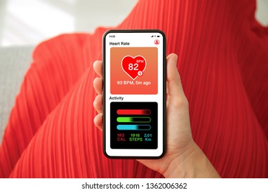 female hands in red dress holding phone with app heart and activity on the screen