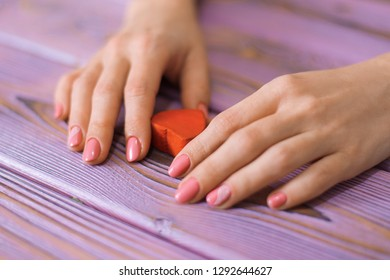 Female hands and red heart on a wooden background.