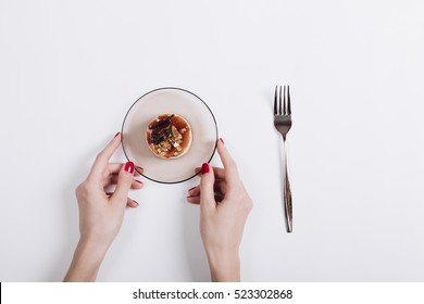 Female hands with red manicure holding saucer with cake, next is fork, top view, white background