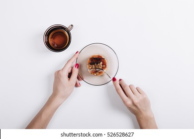 Female hands with red nail polish cut the cake with a fork, top view
