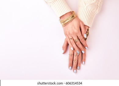 Female hands in rings and bracelets on a white background. Beautiful blue manicure. Many different costume jewelery.